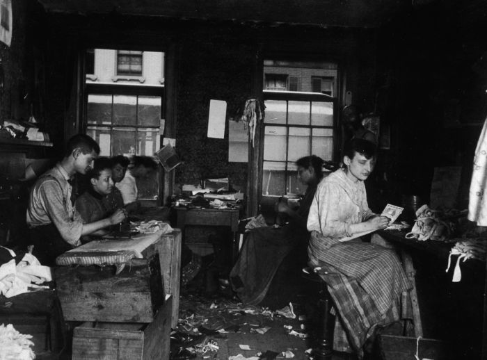 circa 1890: Men and women make neckties inside a tenement on Division Street, Little Italy, New York City. (Photo by Jacob A. Riis/Museum of the City of New York/Getty Images)