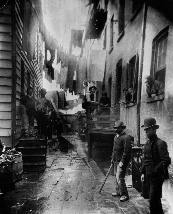 "1887: A group of men loitering in an alley known as ""Bandits' Roost"", situated off Mulberry Street in New York City. (Photo by Jacob A. Riis/Museum of the City of New York/Getty Images)"