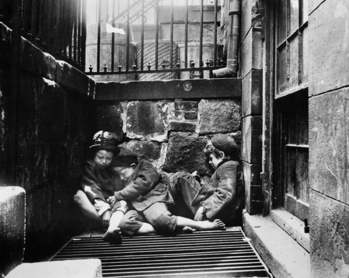 Three young street arabs huddle together for warmth in an areaway, Mulberry St, New York. (Photo by Jacob A Riis/Getty Images)